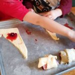 rolling ham and cranberry sauce in crescent roll dough